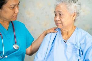 médico que usa estetoscopio para verificar que el paciente asiático mayor o anciano usa una mascarilla en el hospital para proteger la infección por el coronavirus covid-19. foto