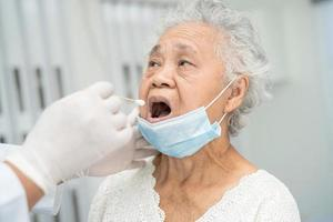 Doctor in pep suit taking a throat and nasal swab from senior asian woman patient to test covid-19 coronavirus infection. photo