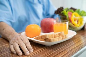 Asian senior or elderly old lady woman patient eating breakfast vegetable healthy food with hope and happy while sitting and hungry on bed in hospital. photo