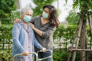 Asian senior or elderly old lady woman walk with walker and wearing a face mask for protect safety infection Covid-19 Coronavirus. photo
