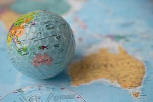 Bangkok, Thailand, May 1, 2021 Australia map at golf ball with flag on world globe map. photo