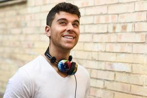Young man in urban background listening to music with headphones photo