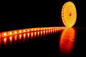 cinta decorativa de diodos para iluminación, un rollo de tira de led con luz cálida amarilla en el suelo laminado foto