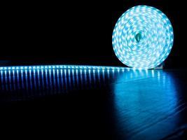 Bobina de tira de led para iluminación decorativa, tira de diodos con luz fría azul sobre fondo oscuro foto
