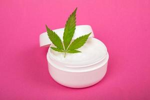 cosmetic skin care cream with hemp extract on pink background photo