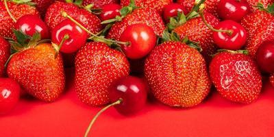 Cereza dulce y fresas sobre un fondo rojo cerrar foto