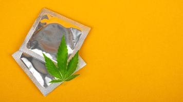 condom and cannabis leaf with copy space on yellow background, sex drugs mockup photo