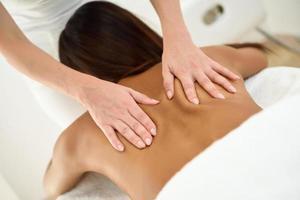 mujer árabe recibiendo masaje de espalda en el centro de bienestar spa. foto