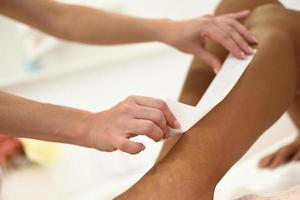 Woman having hair removal procedure on leg applying wax strip photo