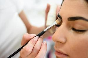maquilladora poniendo sombra de ojos en una mujer africana. foto