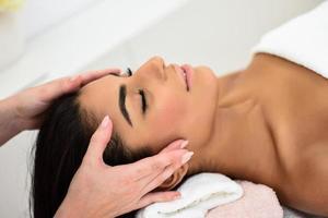 mujer recibiendo masaje de cabeza en el centro de bienestar spa. foto