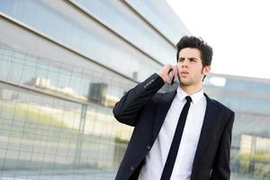 Attractive young businessman on the phone in an office building photo