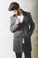 Handsome young man wearing coat. Studio shot photo