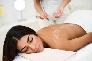 Woman receiving back massage treatment with oil brush in spa wellness center photo