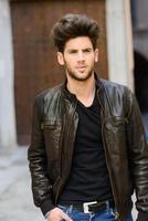 atractivo joven guapo, modelo de moda en el fondo urbano foto