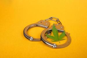 esposas y una hoja de cannabis sobre fondo amarillo, arresto por distribución ilegal de marihuana foto
