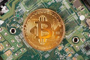 Moneda bitcoin de cerca en el fondo de la placa base foto