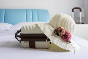 Hat and luggage on bed in the bedroom photo