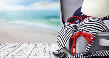 Bikini and clothes in luggage on white wooden photo