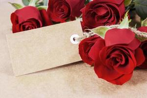 Red roses with blank paper tag on brown paper photo