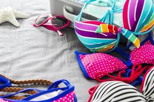 Bikinis and clothes in luggage on the bed photo