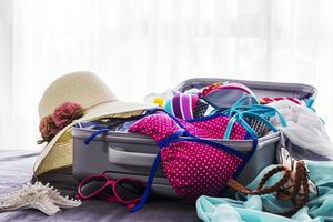Pink bikini and clothes in suitcase on the bed photo