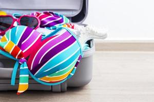 Colorful bikini and clothes in luggage on the laminate floor photo