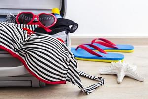 Bikini and clothes in luggage on the laminate floor photo