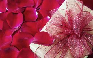 Caja de regalo sobre fondo de pétalos de rosa roja foto