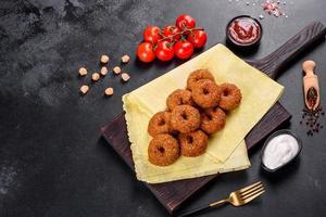 Hermoso delicioso falafel de garbanzos frescos con salsas sobre un fondo de hormigón foto