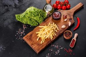 papas fritas calientes frescas con verduras saladas y especias foto