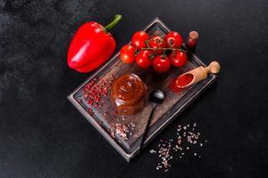 condimento picante de la cocina georgiana adjika en un recipiente con pimiento rojo y ajo foto
