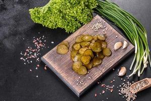 Sabroso pepino encurtido picante salado cortado con anillos sobre una tabla de cortar de madera foto