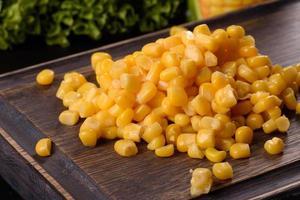 Delicioso maíz enlatado suelto fresco sobre una tabla de cortar de madera foto