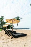 Silla de playa vacía con palmeras en la playa con fondo de mar foto