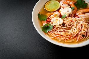 Noodles with spicy soup and shrimps or Tom Yum Kung - Asian food style photo