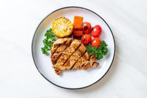 Grilled and barbecued fillet pork steak with corn, carrot, and tomatoes photo