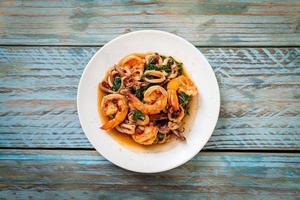mariscos salteados de camarones y calamares con albahaca tailandesa - estilo de comida asiática foto