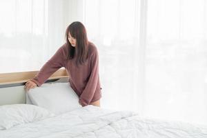 Mujer asiática haciendo la cama en la habitación con sábana blanca limpia foto