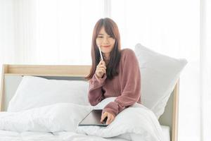 Beautiful Asian woman working with tablet on bed photo