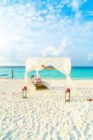 Wedding arch on the beach with tropical Maldives resort and sea background photo