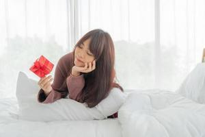 Asian woman happy to receive a gift box or present photo