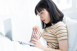 Young Asian woman using laptop to watching tv shows, eating popcorn at home photo