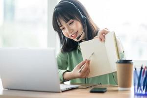 hermosa dama asiática de servicio al cliente está llamando a los clientes para ofrecer productos foto