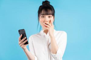 Hermosa mujer asiática sosteniendo el teléfono sobre fondo azul con expresión de sorpresa foto