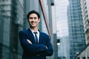 Young Asian businessman with modern building background photo