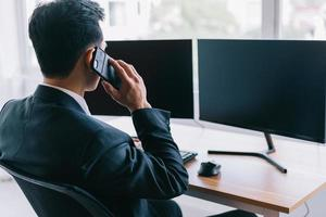 Asian businessman focused on working while on the phone photo