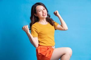 Hermosa mujer asiática con estilo activo sobre fondo azul. foto