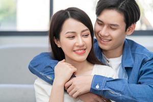 Young Asian couple hugging happily at home photo