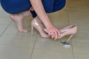 una mujer con un zapato de tacón golpeando la pantalla de su teléfono inteligente. foto